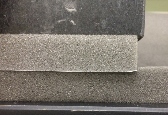 Two pieces of foam compressed by a granite block. The lower piece of foam represents the strop and the upper piece the blade. The interface between these is marked with a sheet of paper.
